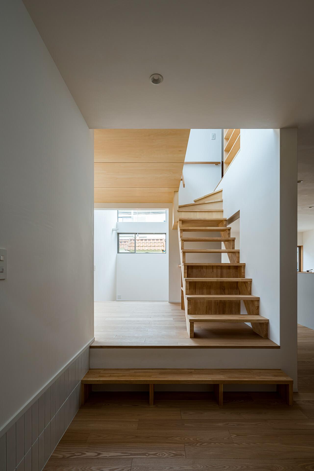 狛江S邸 玄関土間から階段のあるリビング上方向